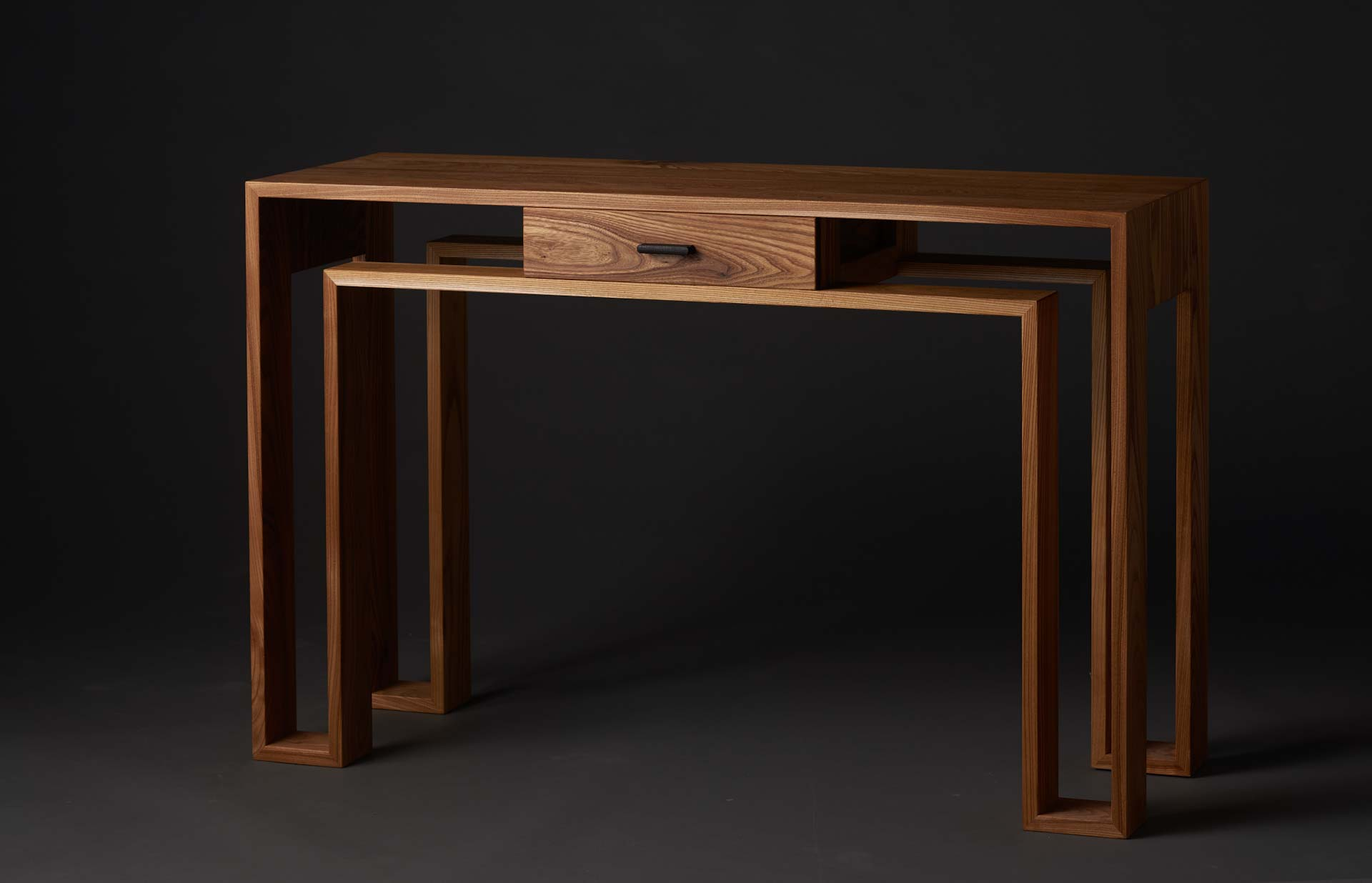 A contenporary styled desk in elm, designed and made by Peter Deij. It has a single drawer and a frame that traces an outline rather than solid legs.